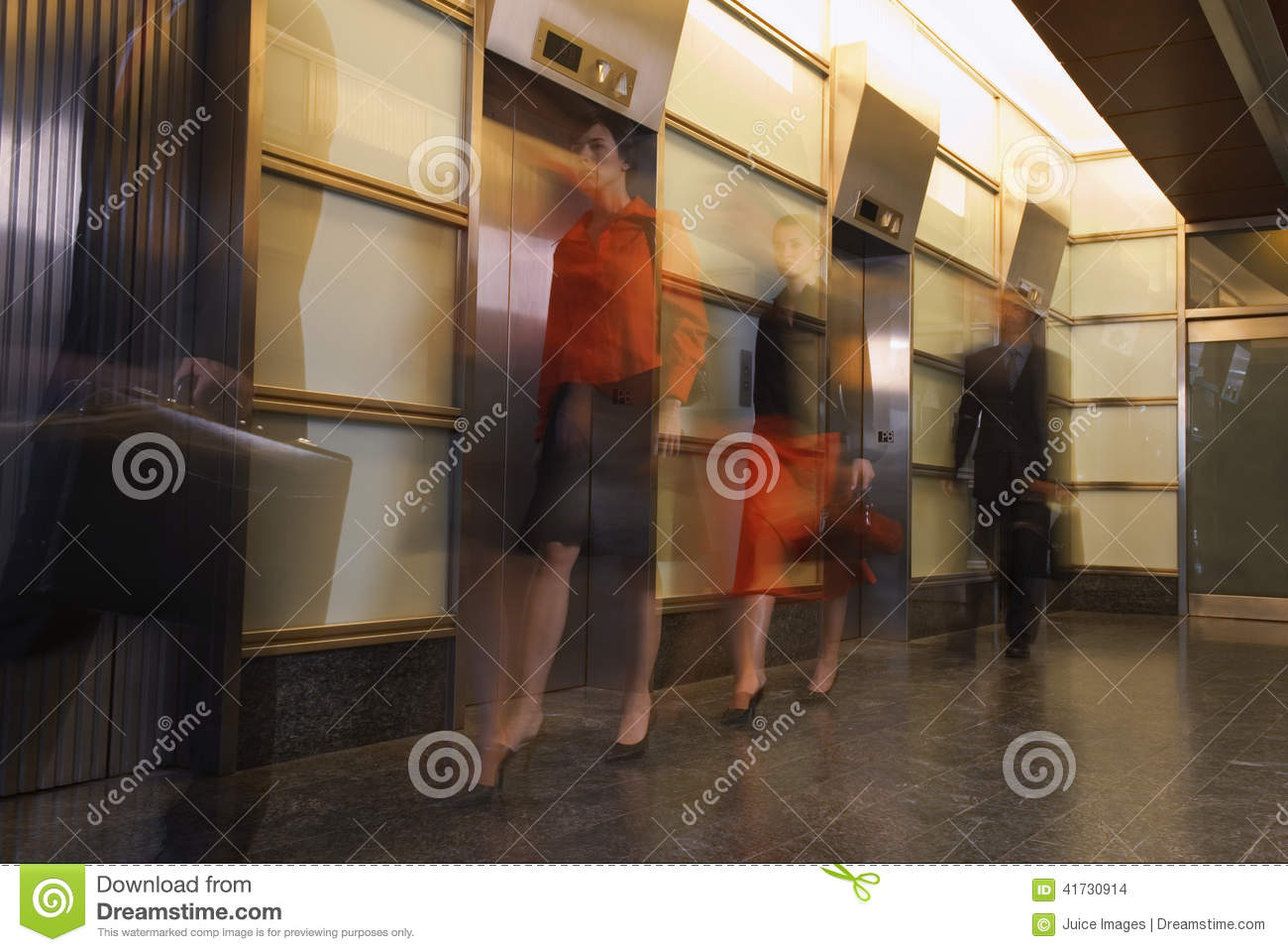 Motion shot of businesspeople walking past elevators