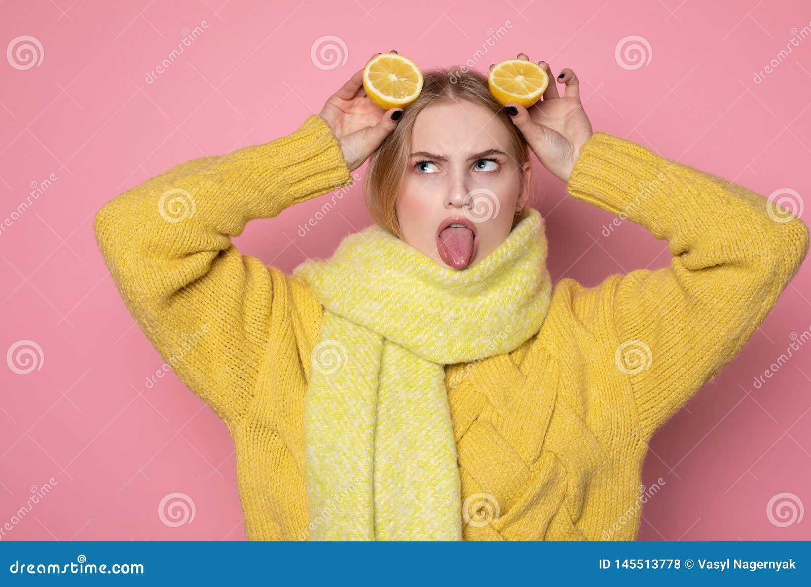 ?motions humaines Belle fille europ?enne blonde dans le visage dr?le jaune d apparence de chandail et d ?charpe, tenant l agrume
