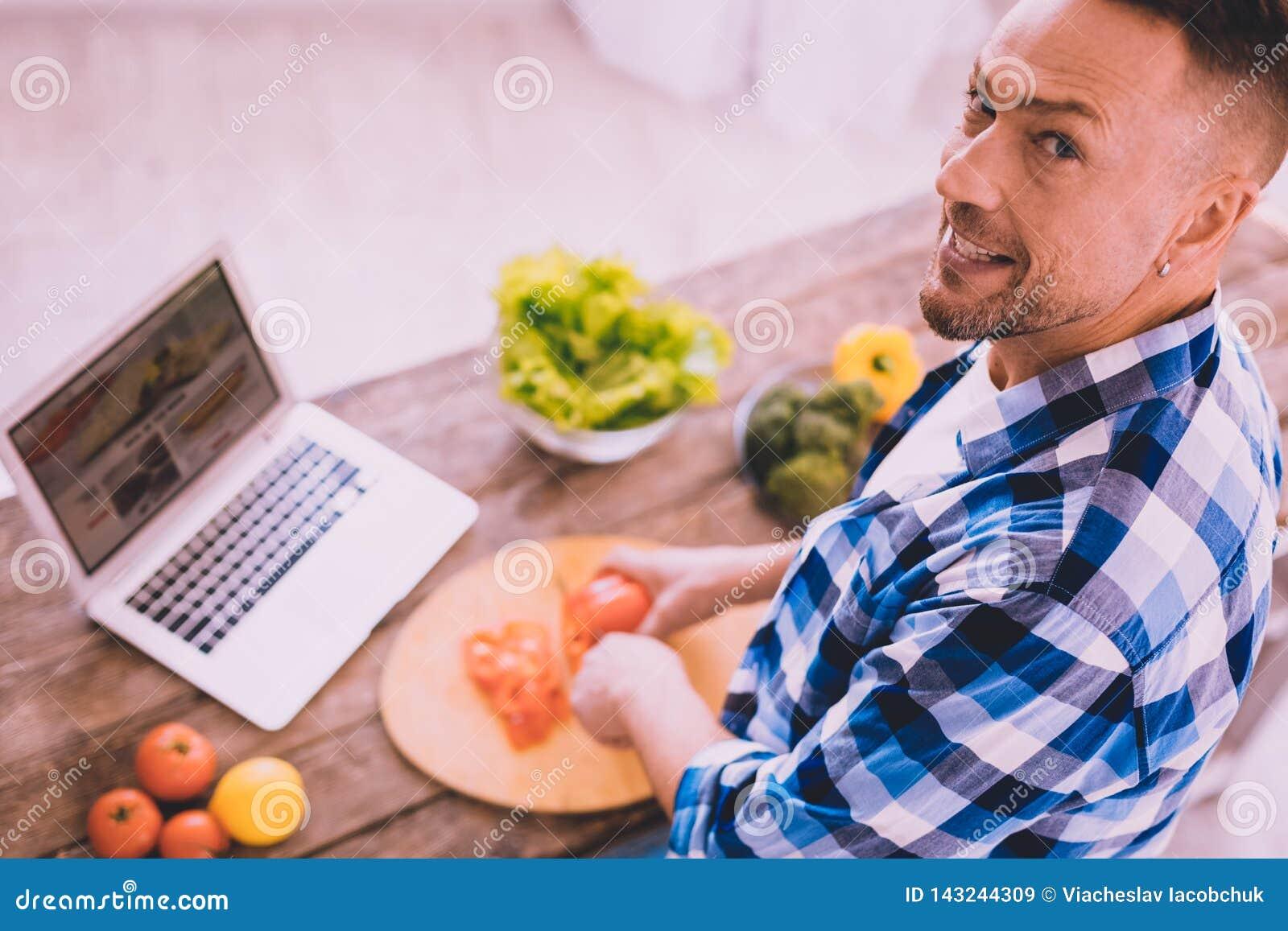Motivierter Mann, der versucht, etwas zu kochen wirklich geschmackvoll