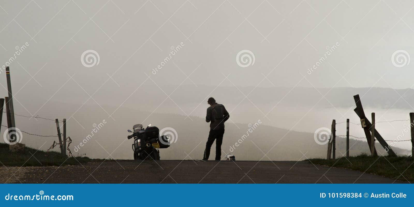 Moto et cavalier debout silhouettés contre une vallée brumeuse
