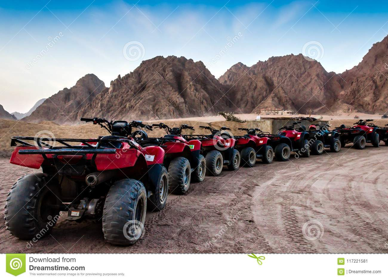 Moto safari in the desert a row of red ATVs on a halt against the background of rocky mountains and a blue sky Egypt