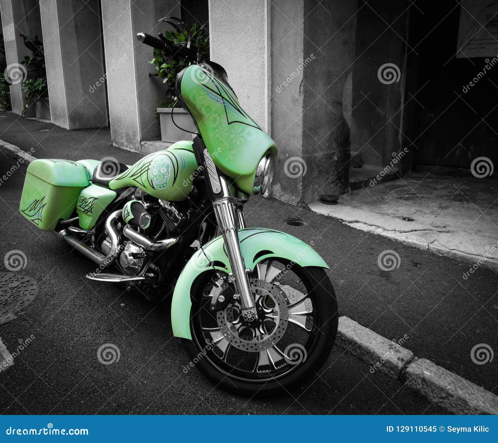 Moto verde en calle negra y blanca