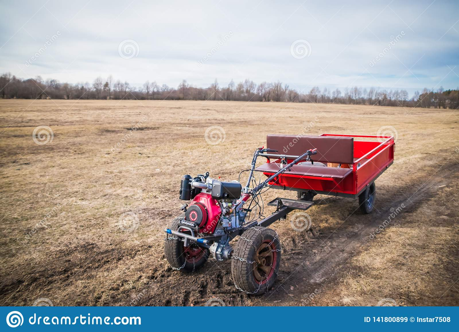 Motoblock med en släp som på våren går på en fältväg i mars, den nya säsongen av fältarbete