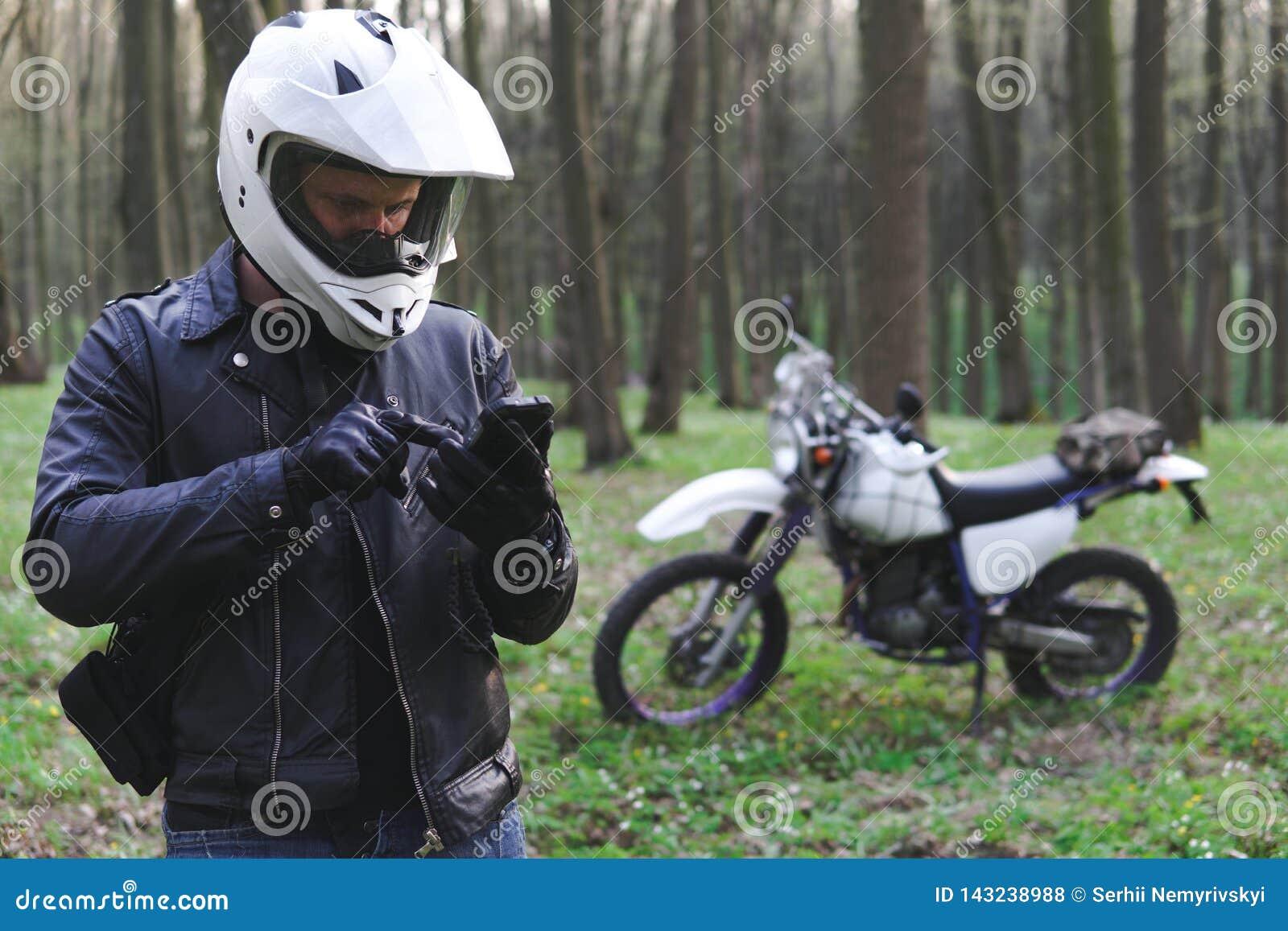 A motocicleta clássica do enduro fora da estrada na floresta da mola, homem em um casaco de cabedal à moda usa um smartphone, eng
