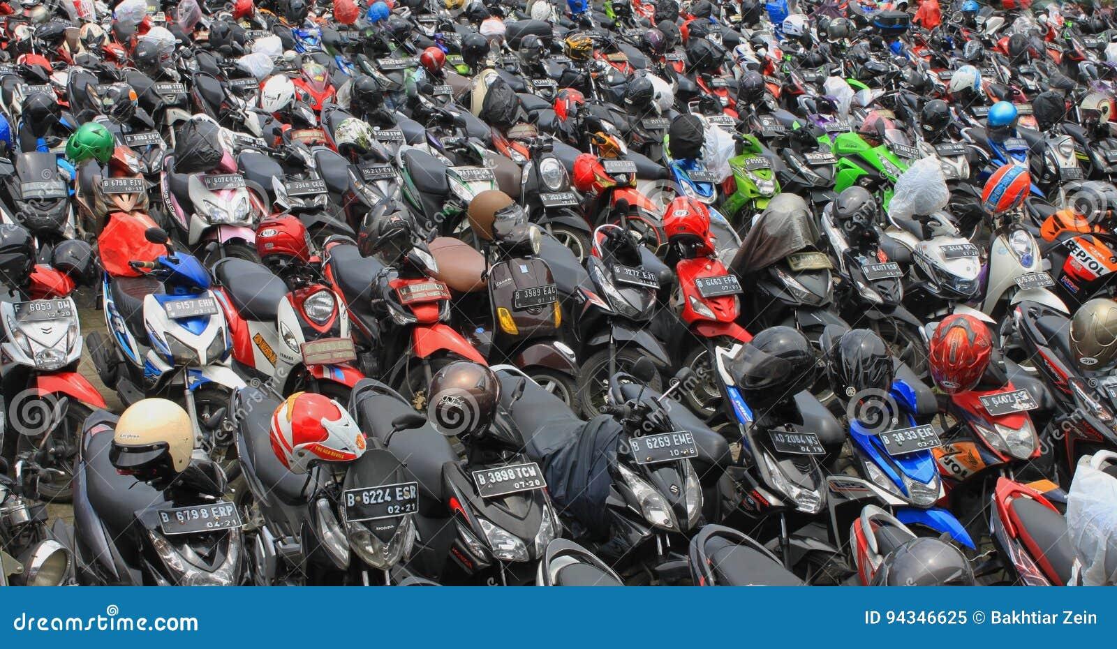 A motocicleta que estaciona completamente muito motor estacionou exterior, vista no transporte de Jakarta Indonésia