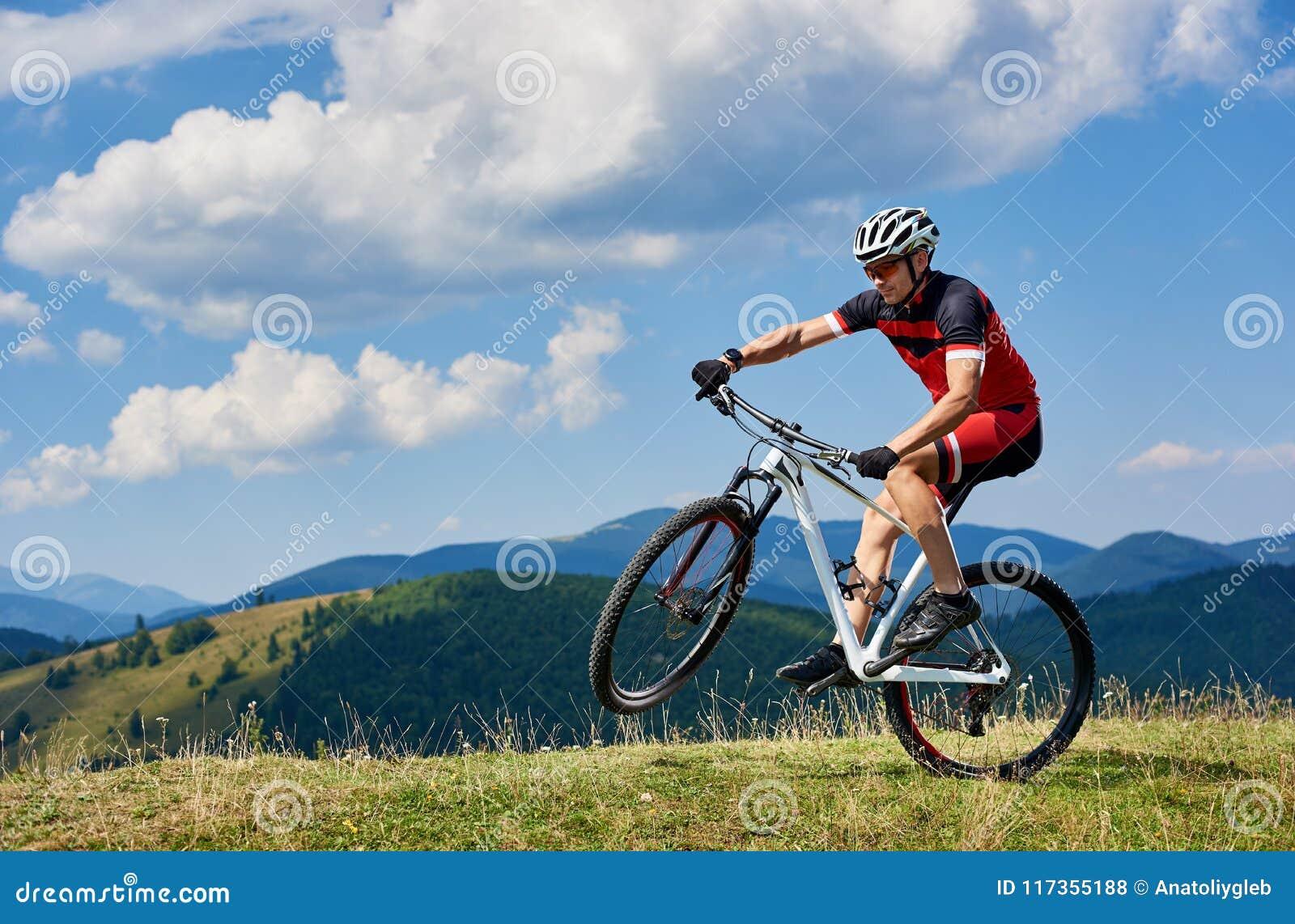 Motociclista atlético novo do turista do desportista no sportswear profissional que gira sobre uma roda da bicicleta