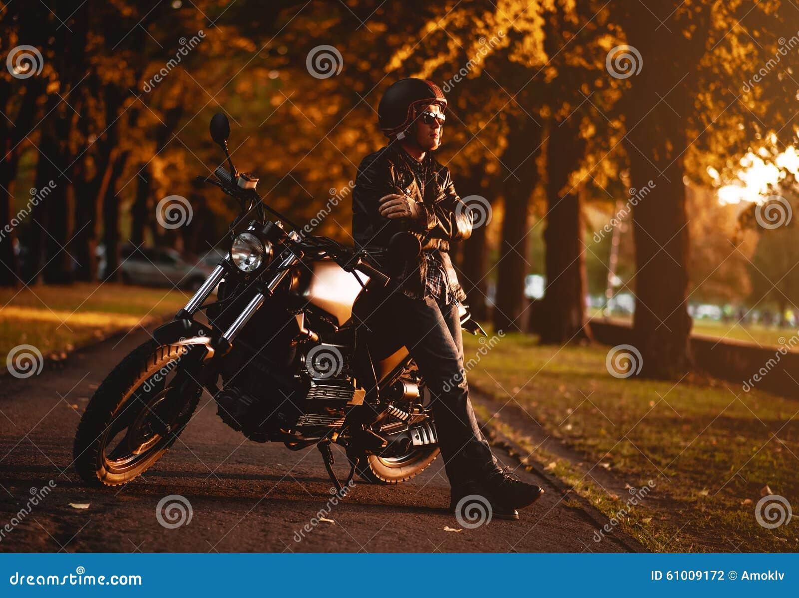 Motociclista com uma motocicleta do café-piloto