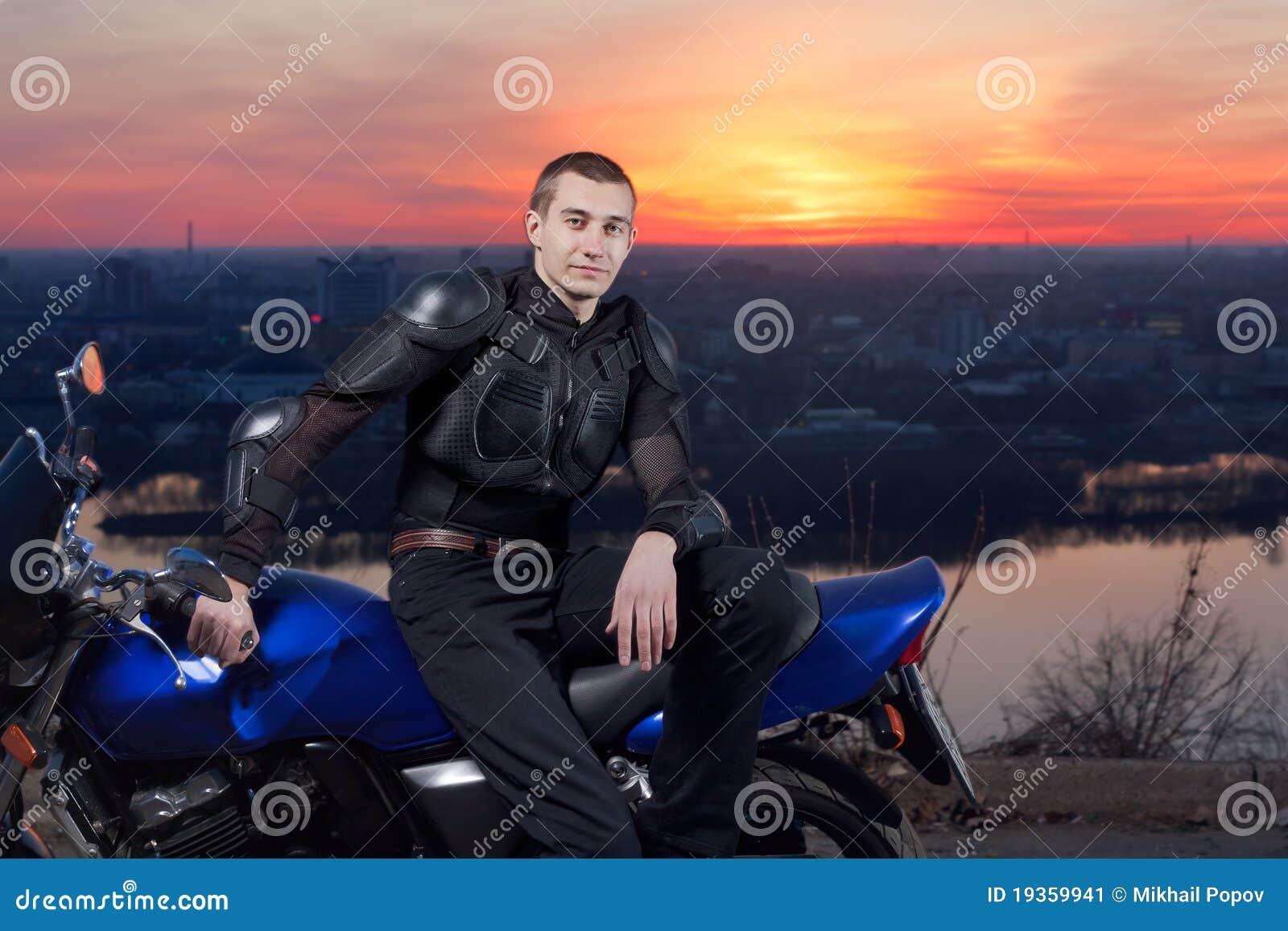 Motociclista de encontro a uma cidade da noite