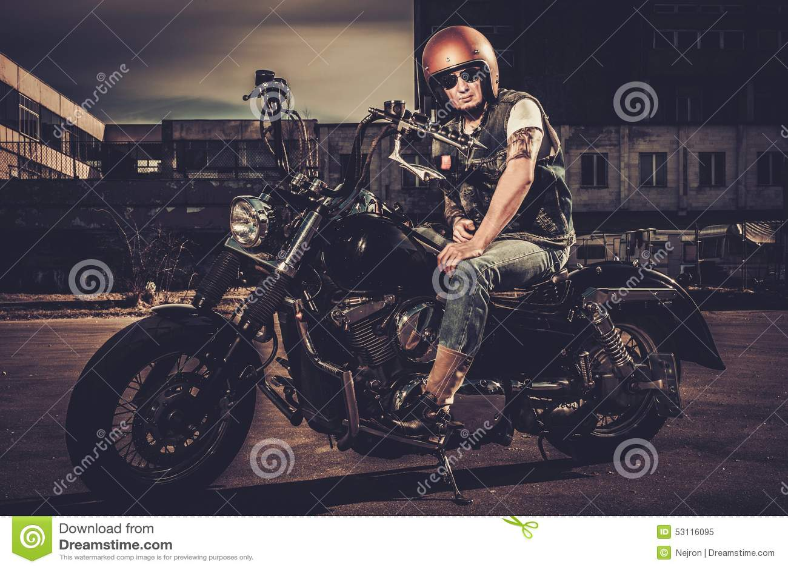Motociclista ed il suo motociclo di stile del bobber