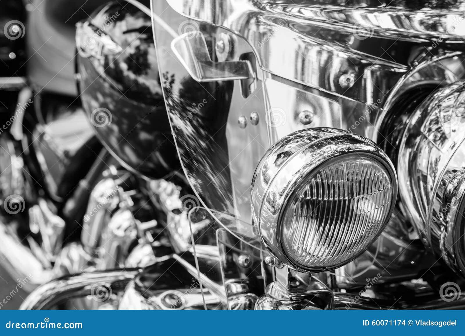 Motociclo brillante del faro su un fondo in bianco e nero confuso