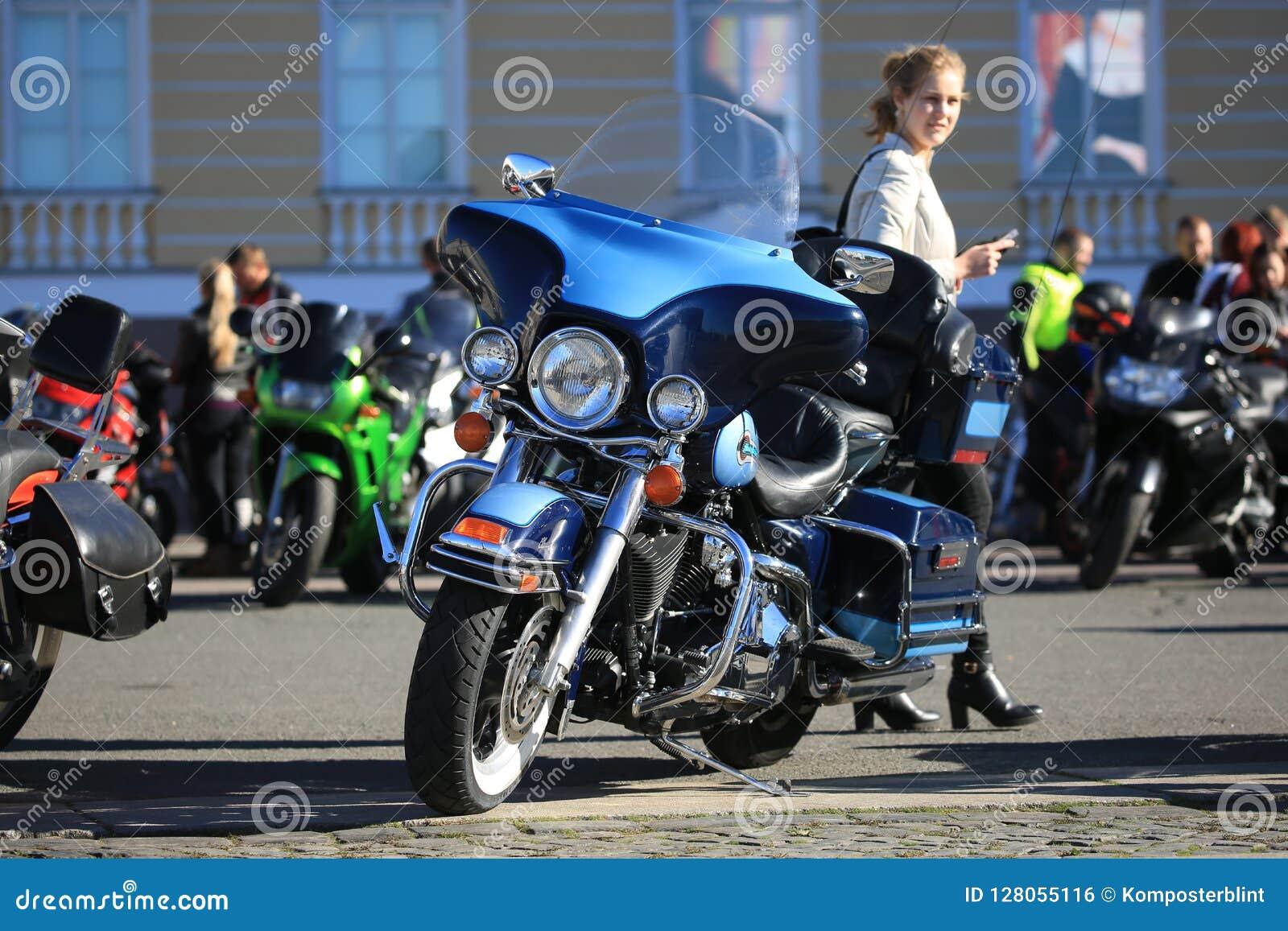 Motociclo e giovane donna parcheggiati di Harley-Davidson da dietro