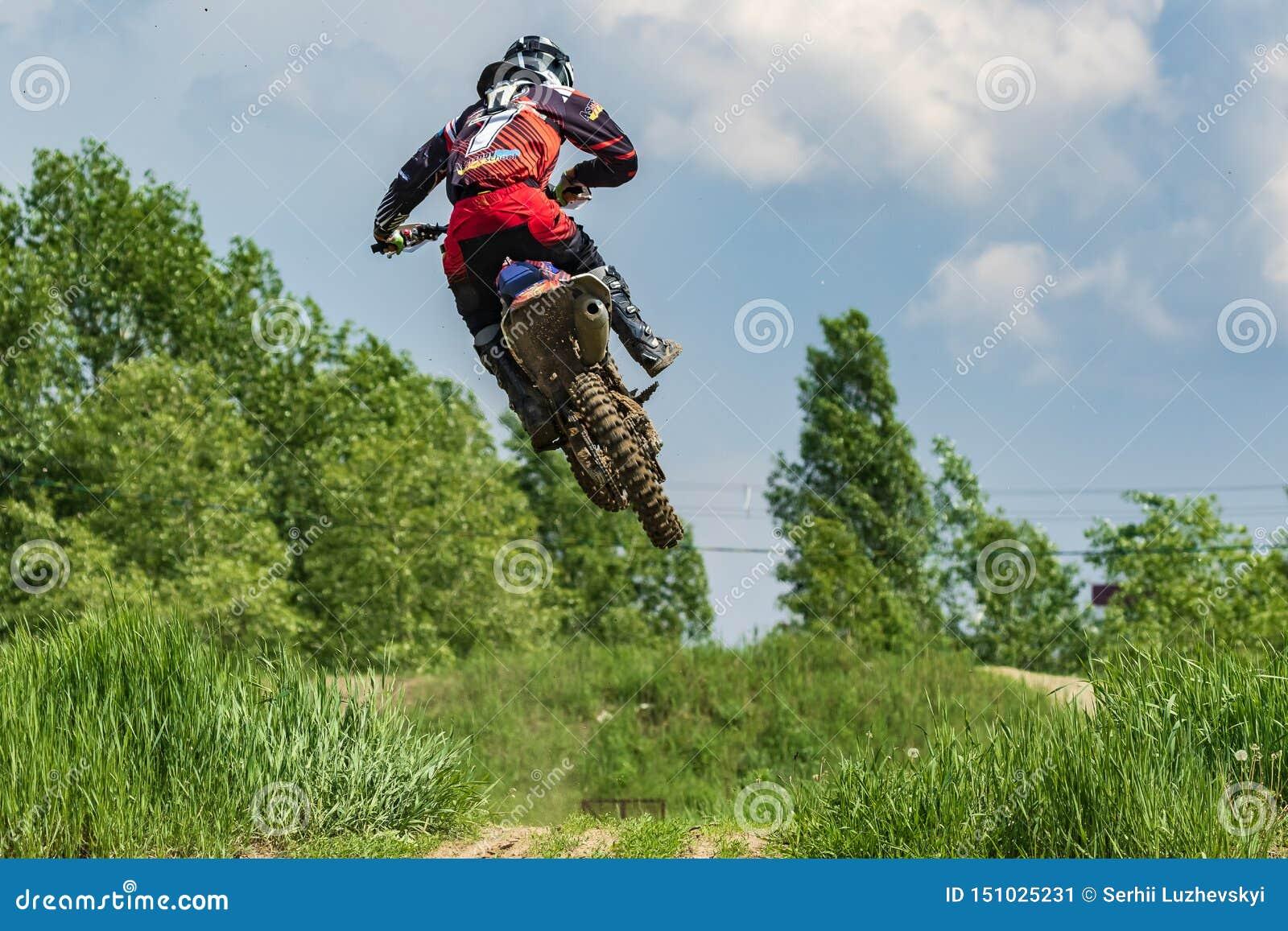 Motocross Der Athlet auf einem Motorradsprungshoch gegen den blauen Himmel und die wei?en Wolken Gegen den Hintergrund hellen Frü