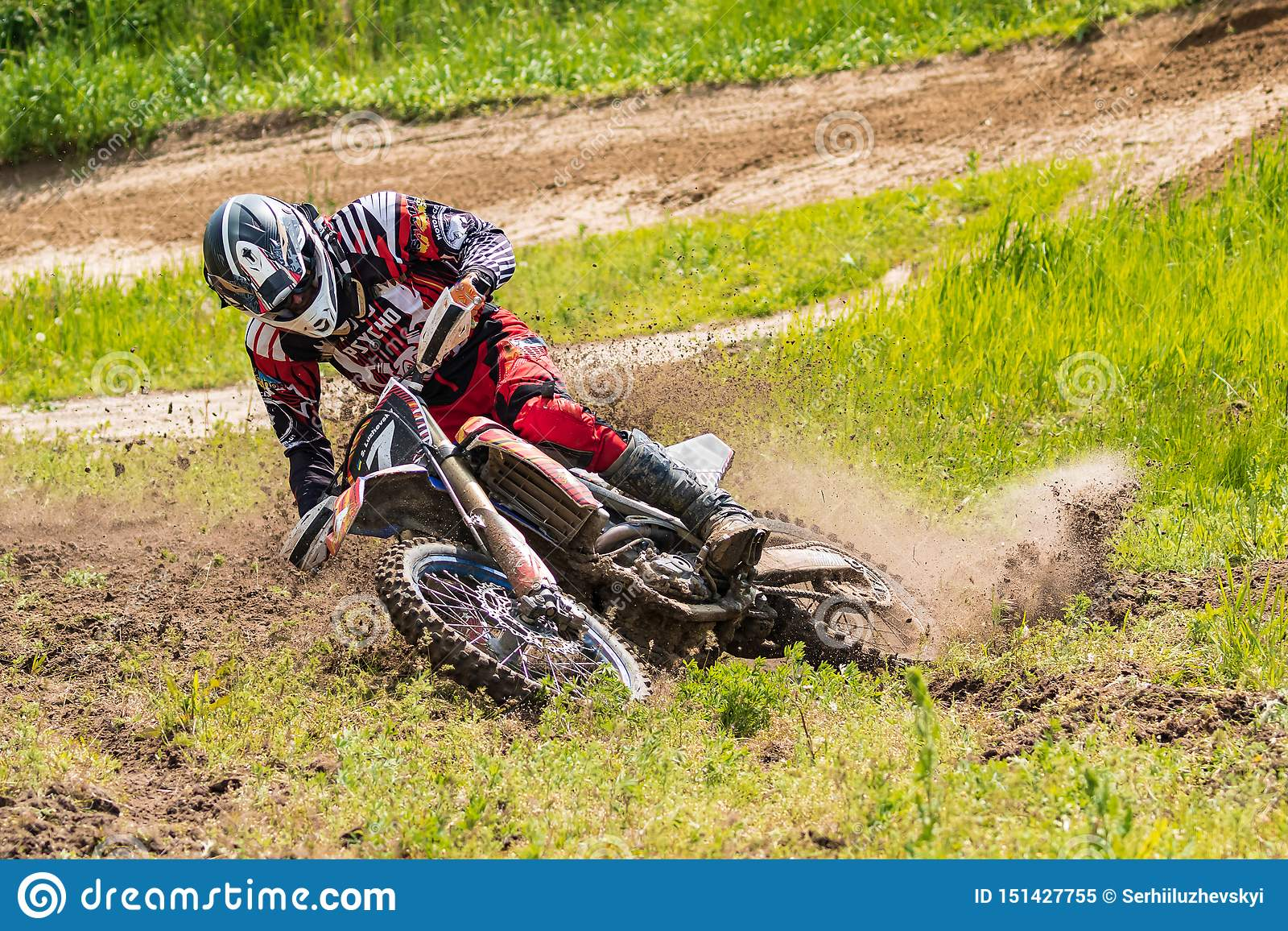 Motocross Motorradfahrer in einer Biegung hetzt entlang einem Schotterweg, Schmutz fliegt von unterhalb der Räder Nahaufnahme