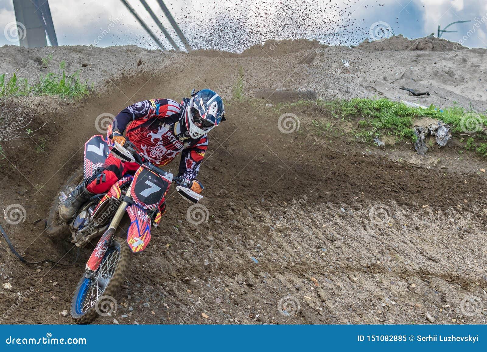 Motocross Motorradfahrer hetzt entlang einem Schotterweg, Schmutz fliegt von unterhalb der R?der Aktiver extremer Rest