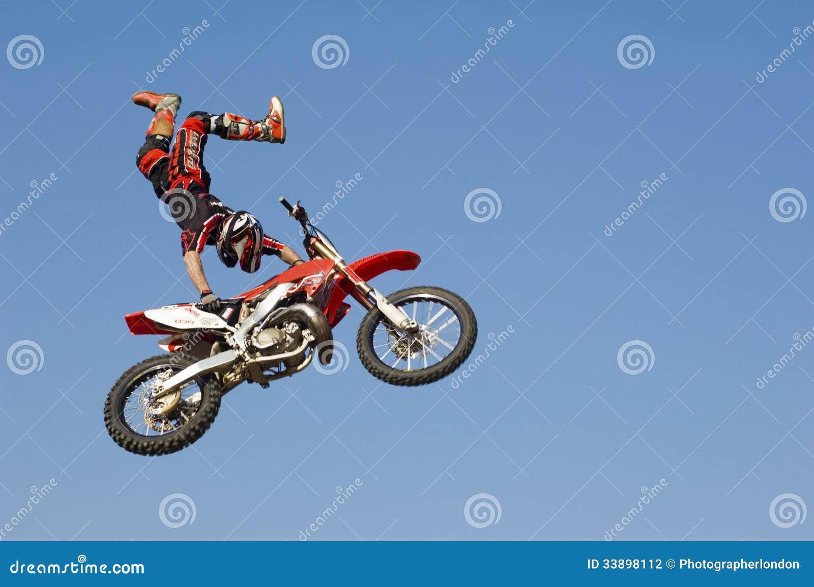 Motocross Racer Performing Stunt With Motorcycle In Midair Against Sky