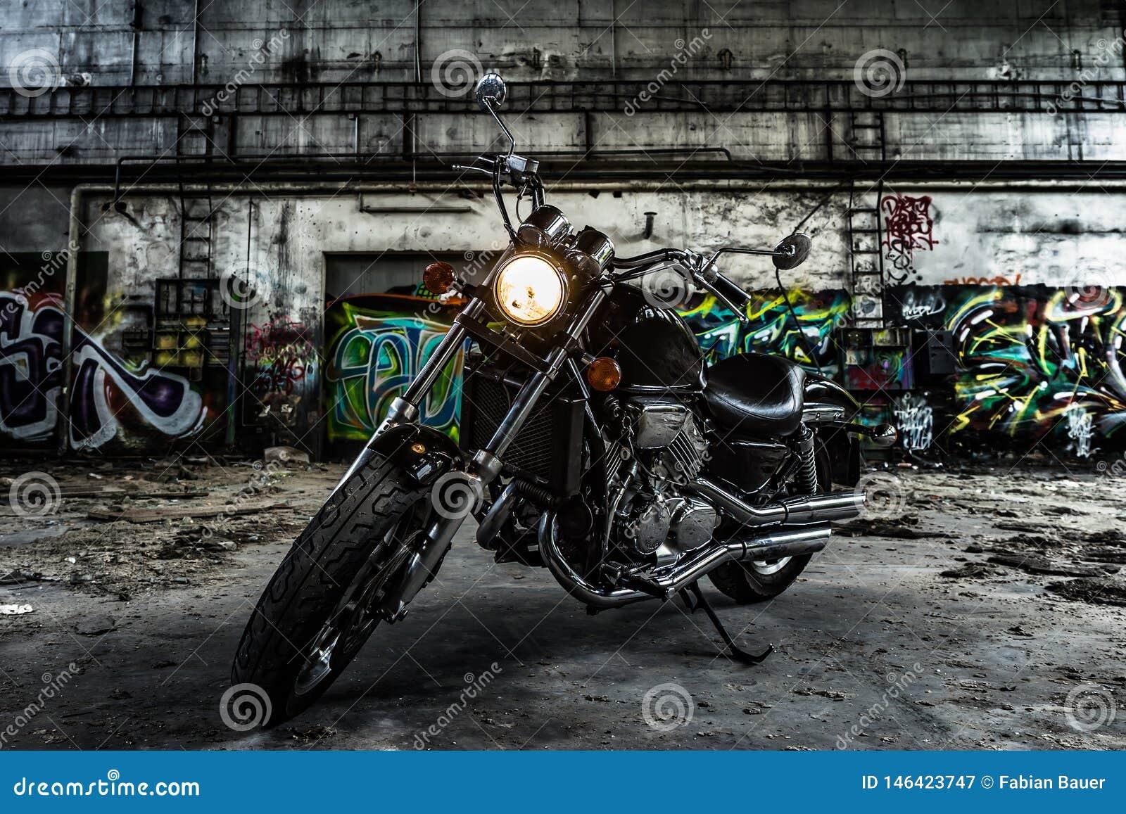 Motocyklu siekacz w starej przemysłowej sali z graffiti miastowymi