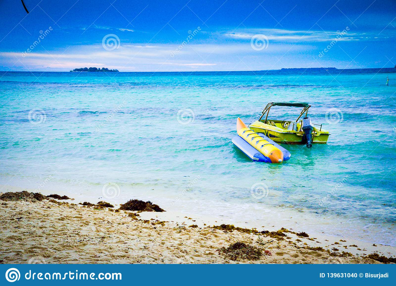 Motor and banana boats in the green sea water ocean under blue cloudy sky