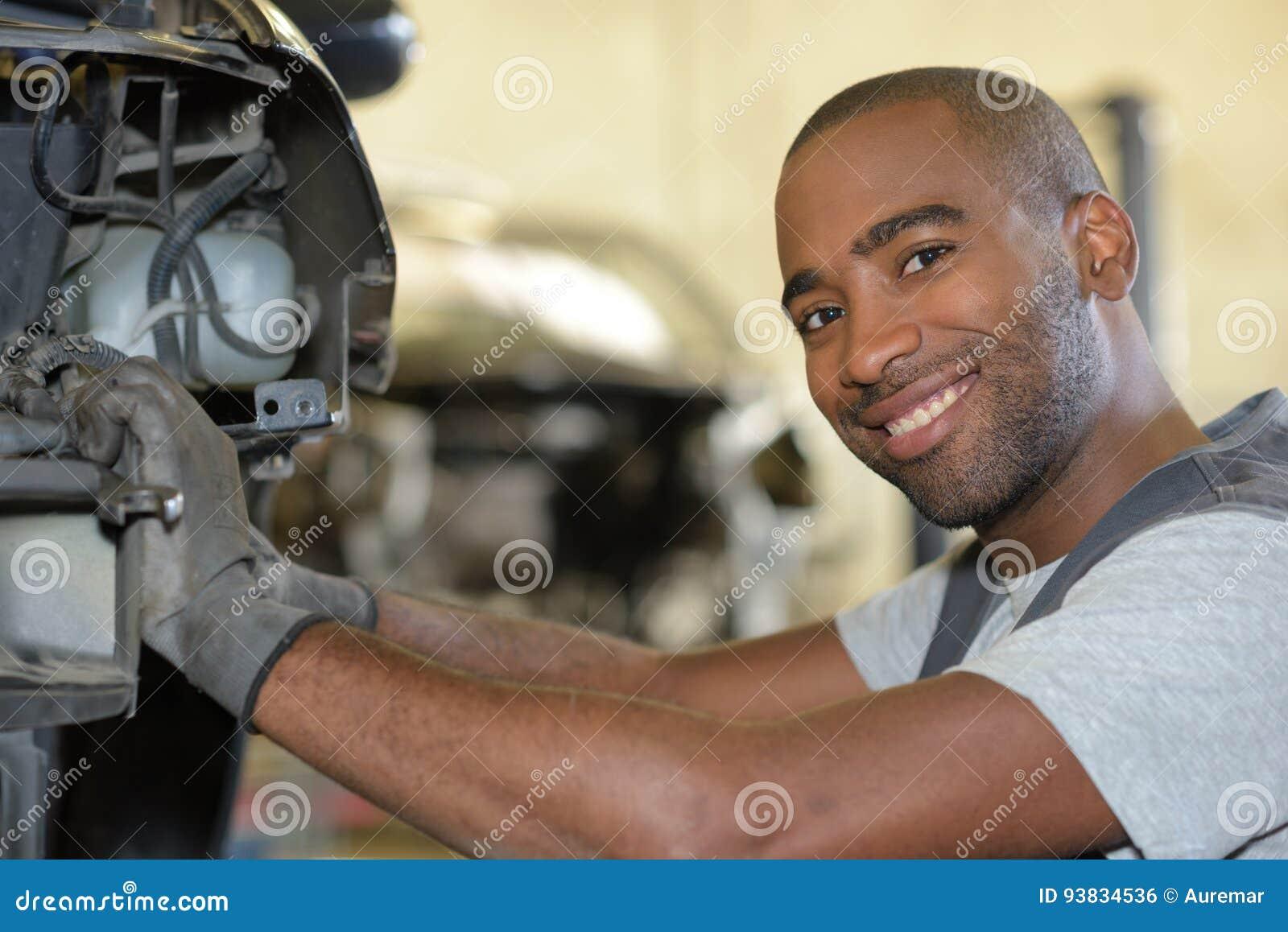 Motor de automóveis de sorriso da fixação do mecânico na garagem