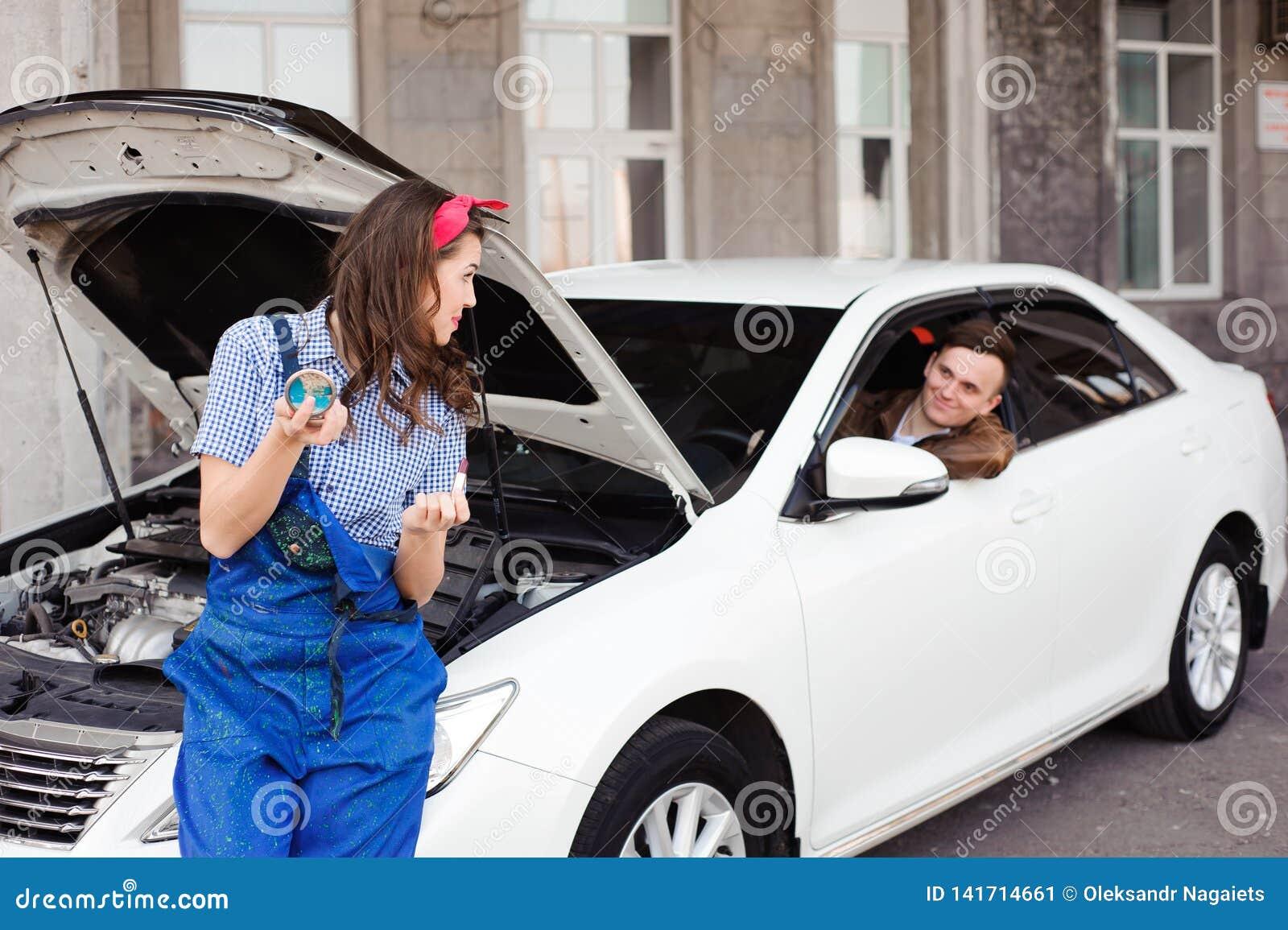 Motor de coche de examen de la muchacha atractiva linda en el taller de reparaciones auto