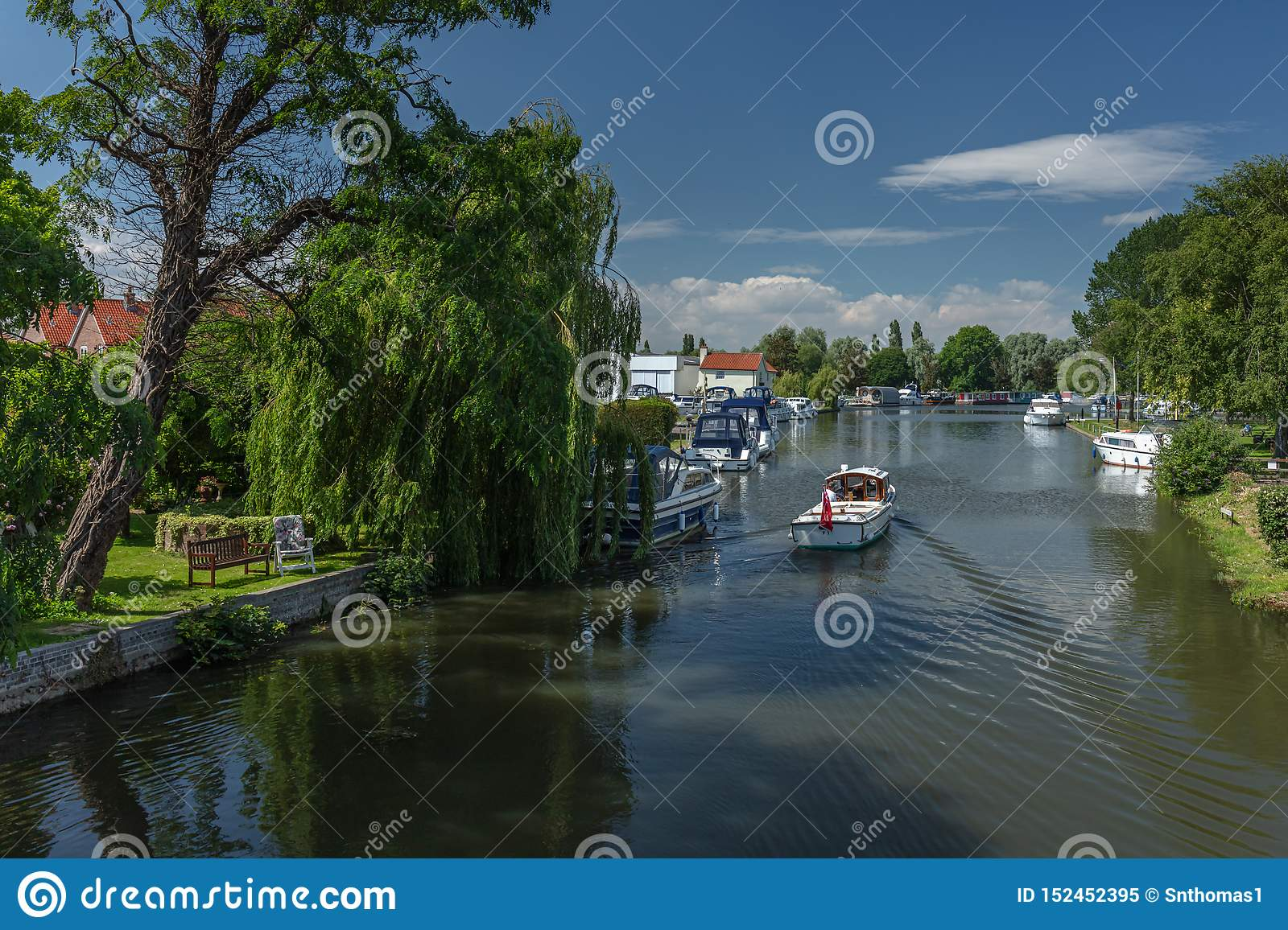 A motorboat cruises towards Beccles Quay on the River Waveney