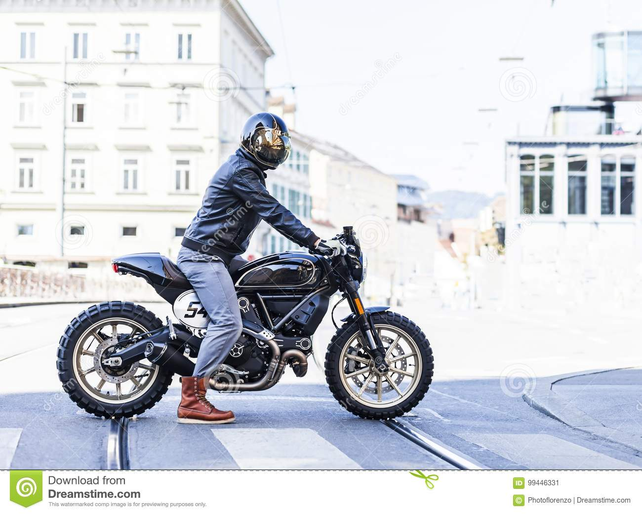 Motorcycle rider on custom made scrambler style cafe racer in th