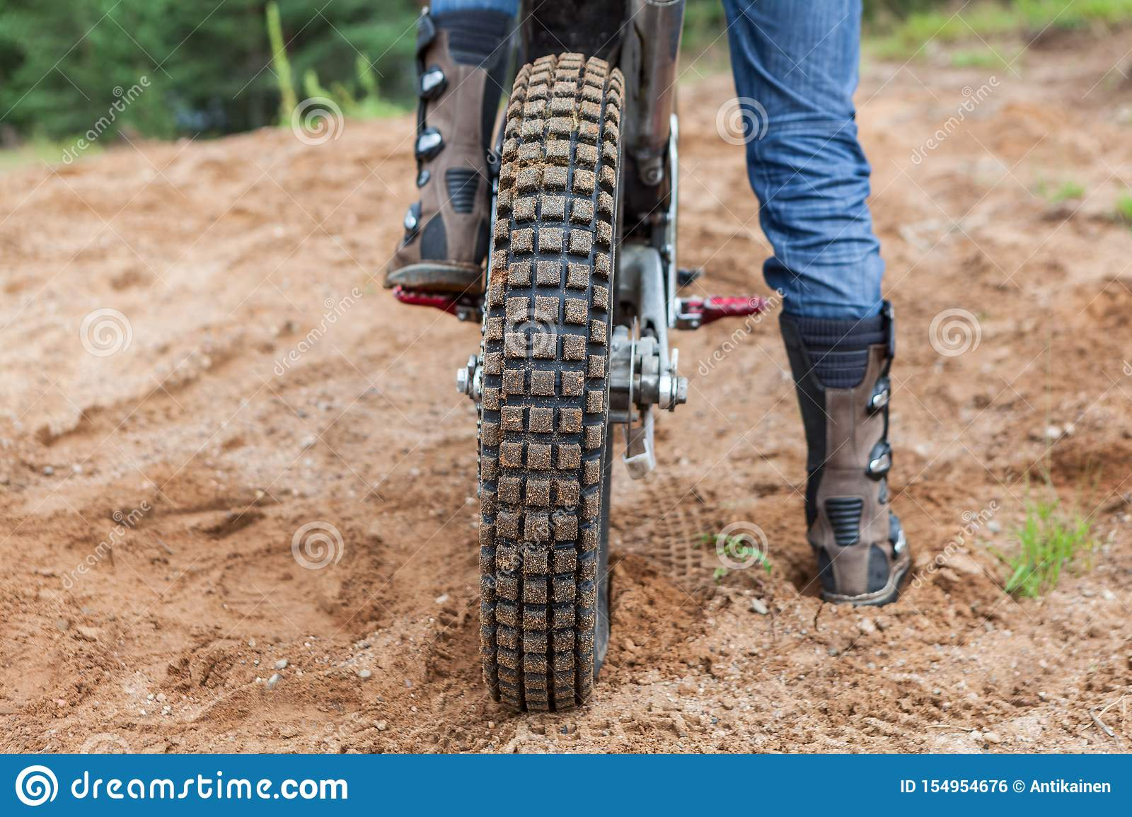 Motorcycle rider has a ride in sand pit, rear view of bike tire and men boots