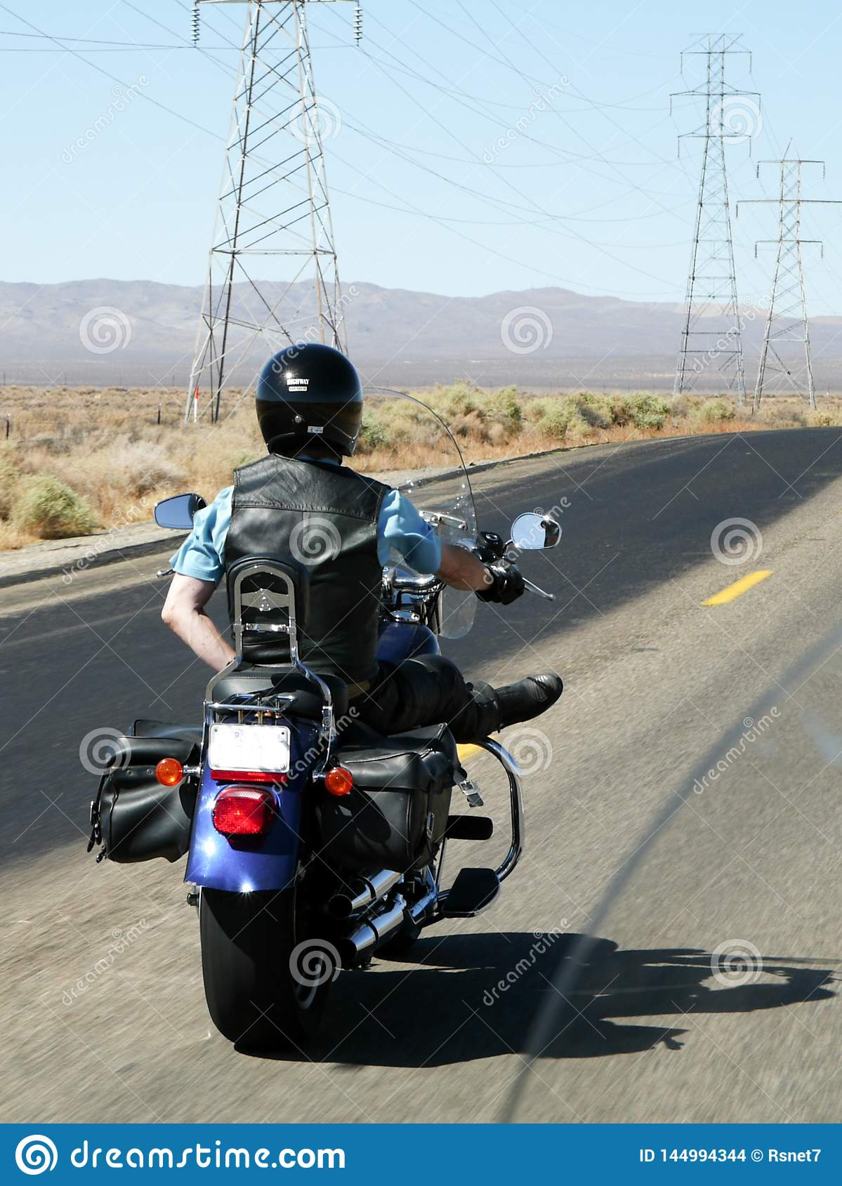 Motorcyclist rides one-handed through the desert