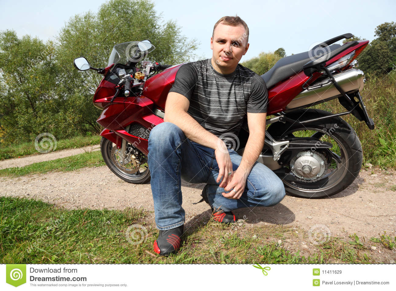 Motorcyclist sitting on country road near bike