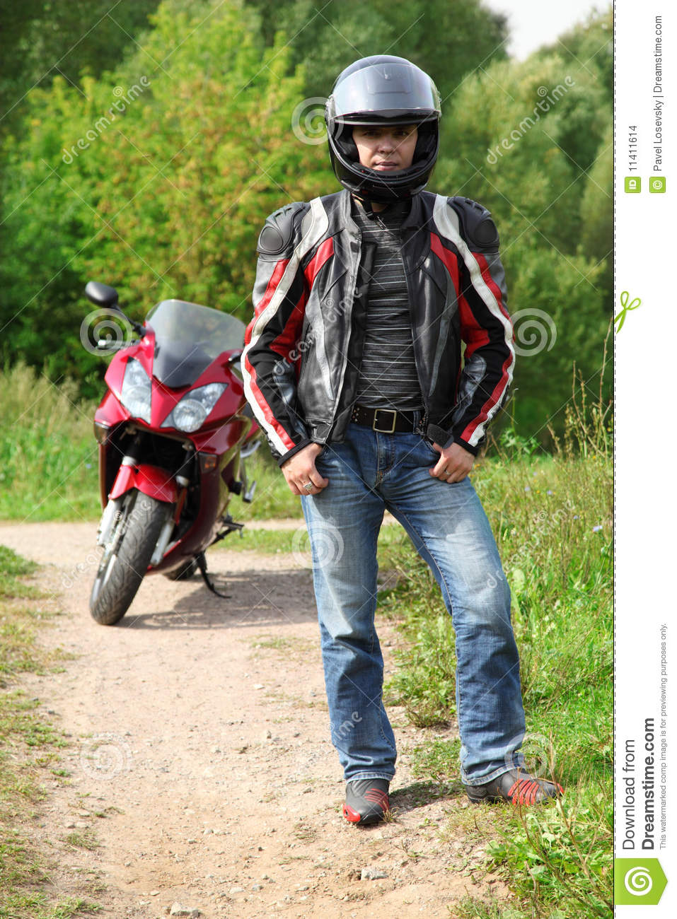 Motorcyclist standing on country road near bike