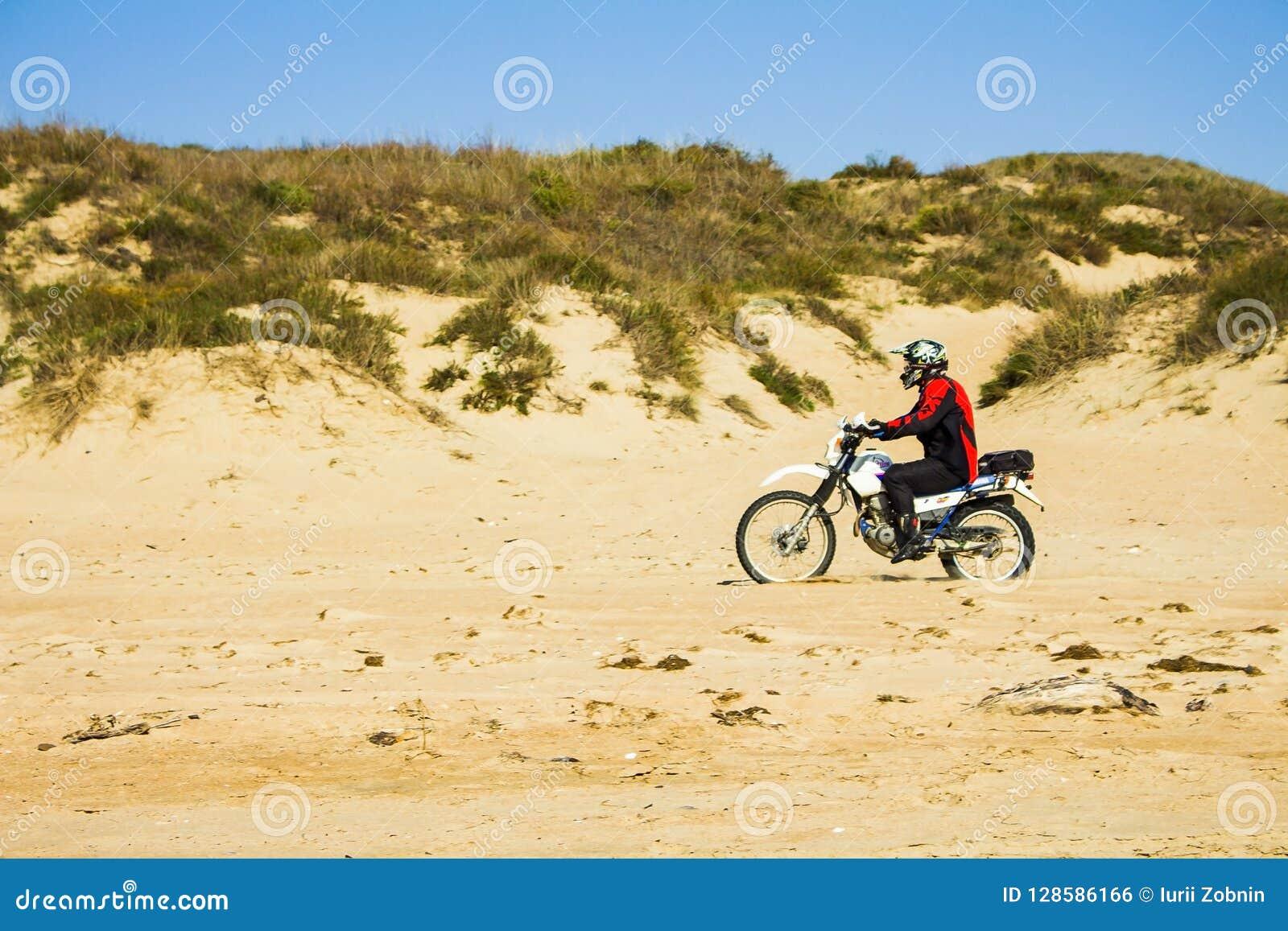 Motorcyklisten rider på sanden på stranden Ryssland, Blagoveshenskaya, 9 oktober 2108