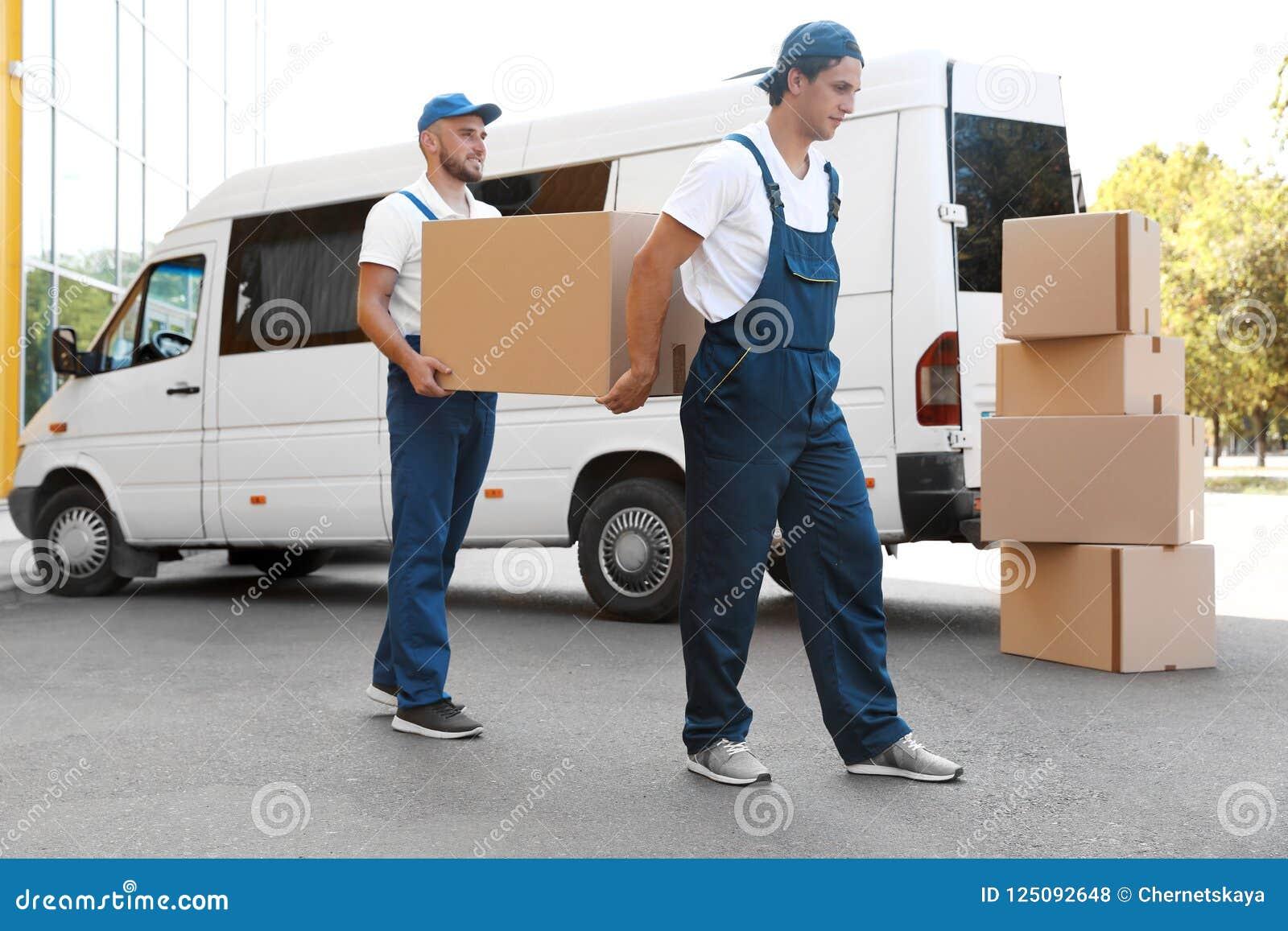 Motores masculinos que descargan las cajas de la furgoneta