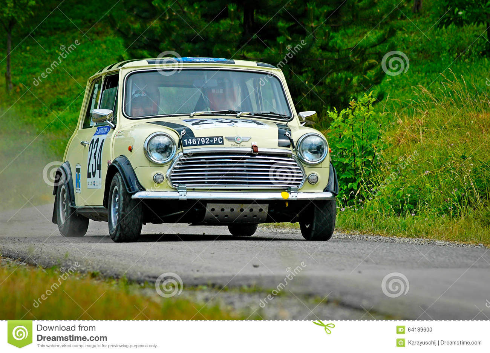 Motoristas não identificados em um carro de competência amarelo de Mini Cooper do vintage