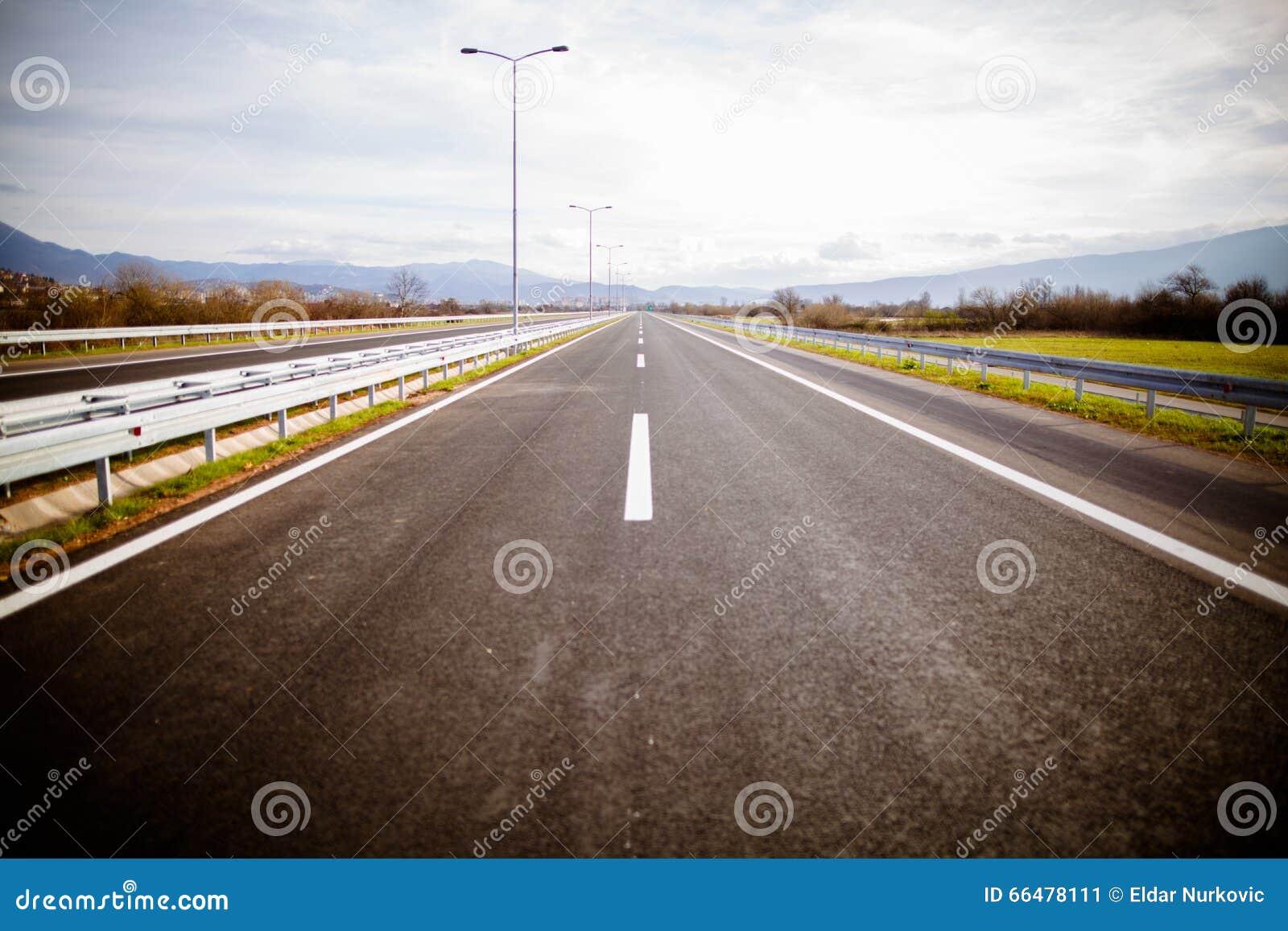 Motorväg på ängar för en ho för solig dag sceniska gröna Motorway som långdistans reser Asfalthuvudvägväg