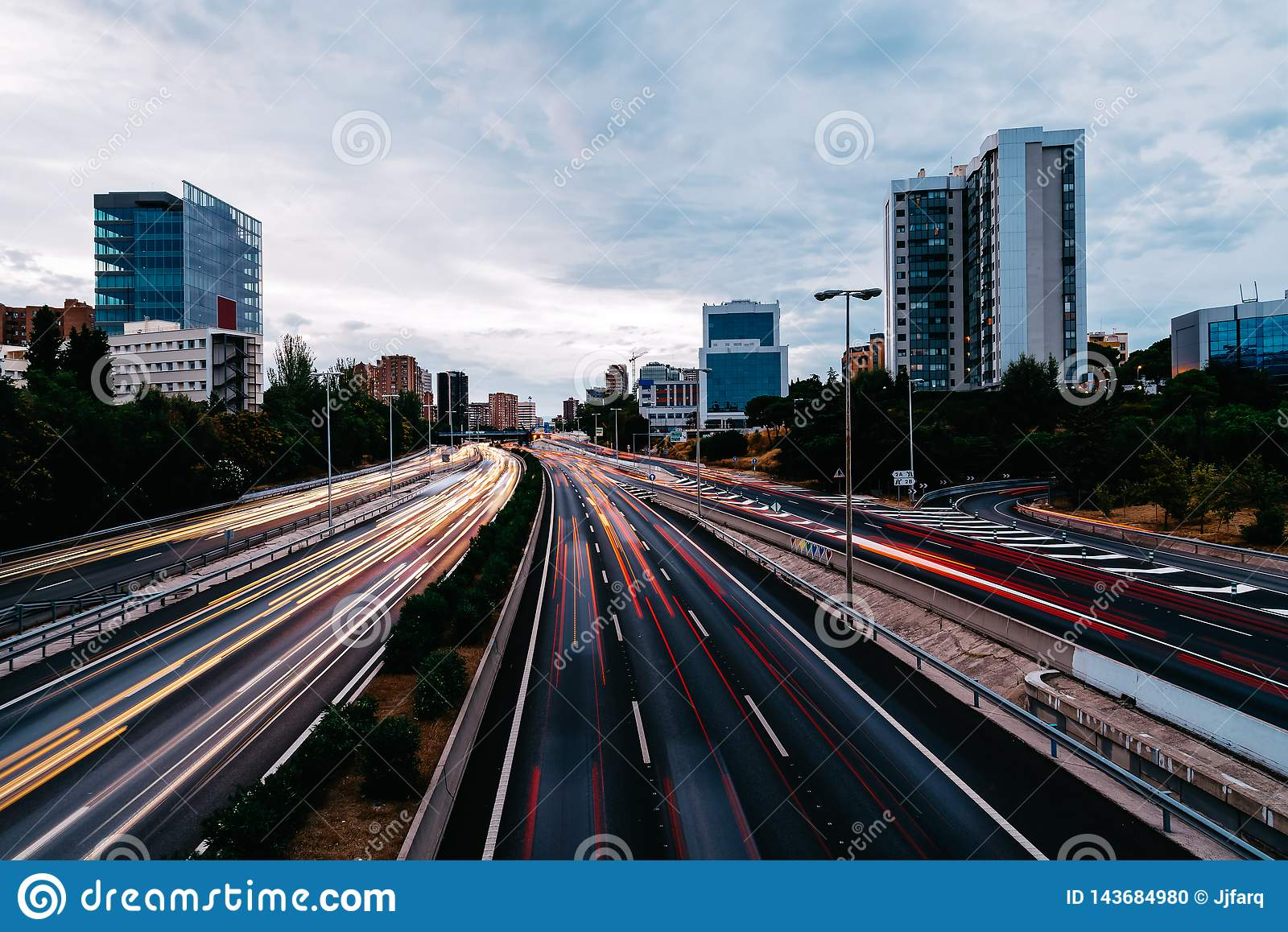 Motorway with light trails at dusk against cityscape