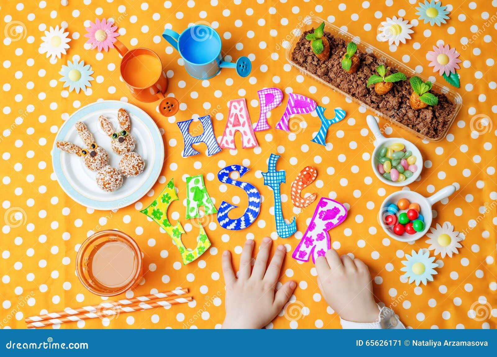 Mots heureux de Pâques avec les mains des enfants et les bonbons et le jus