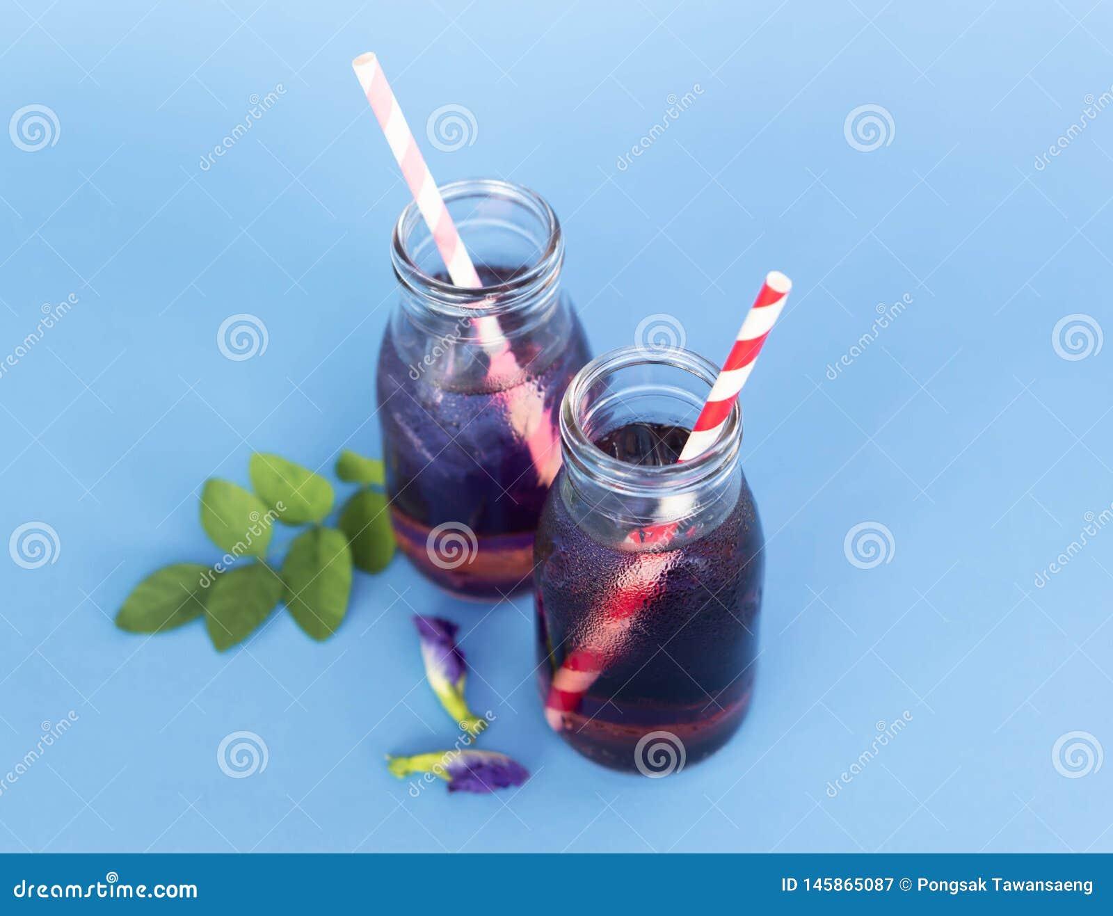 Motyliego grochu sok w trawy butelce z li?ciem i kwiatem na b?awym tle, zielarski dink dla zdrowego poj?cia
