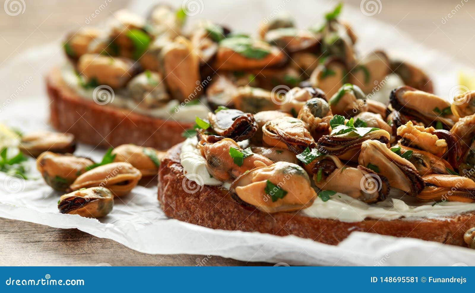 Moules faites maison sur la bruschette grill?e, le pain grill? avec le fromage ? p?te molle et les herbes