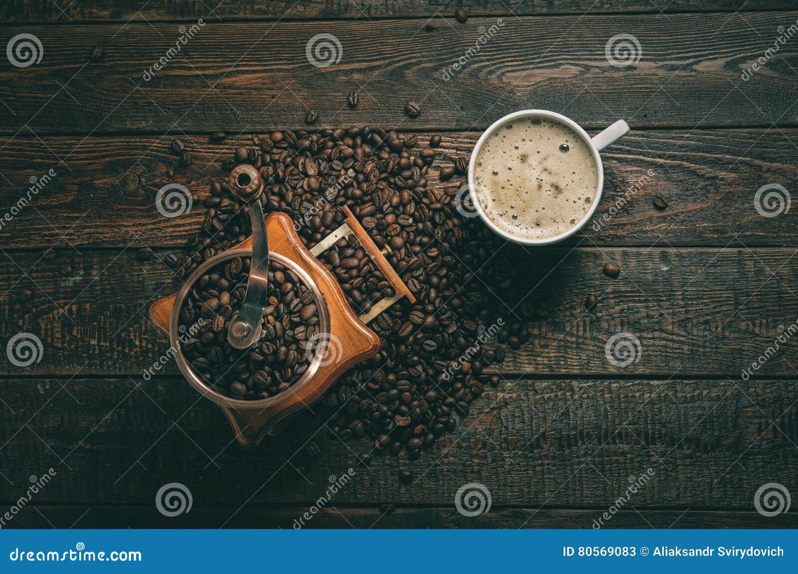 Moulin et tasse à café avec des haricots sur le fond foncé Vue supérieure