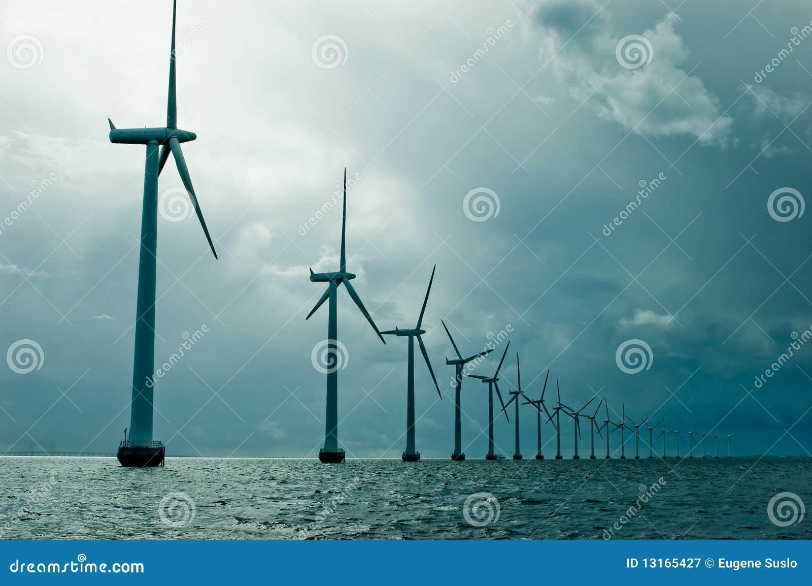 Moulins à vent dans une ligne sur le temps nuageux