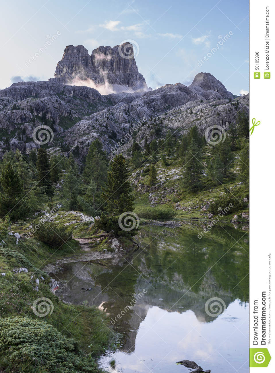 Mount Averau reflected in lake Limedes at sunrise, blue sky with clouds, Dolomites, Veneto, Italy