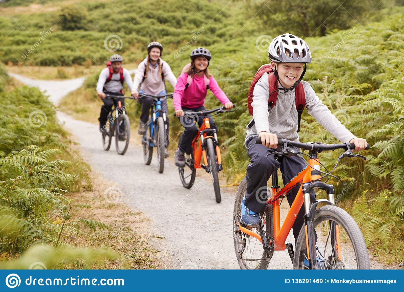 Mountain bike Pre-teen di guida del ragazzo con la suoi sorella e genitori durante il viaggio di campeggio della famiglia, fine s