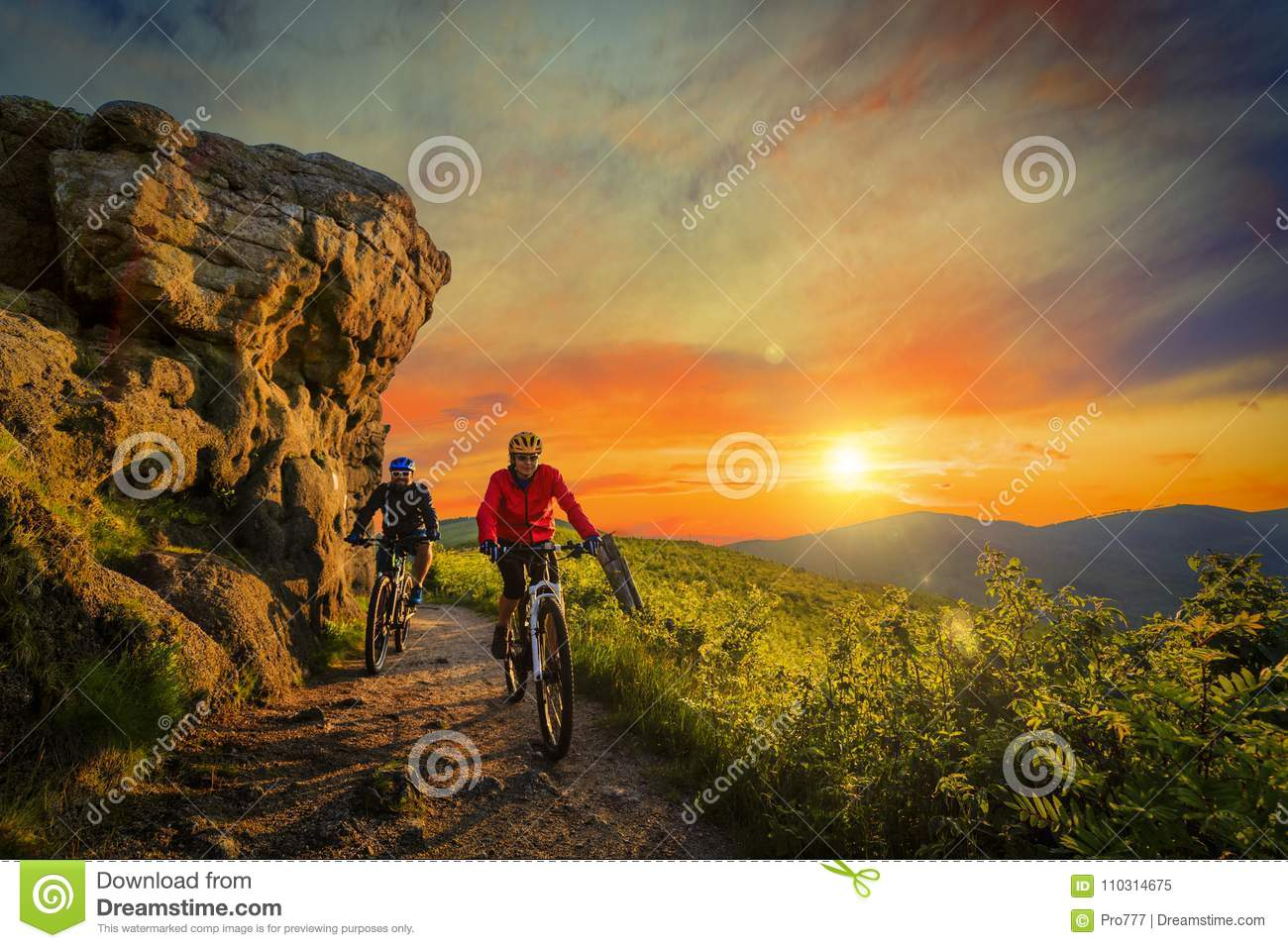 Mountain biking women and man riding on bikes at sunset mountain