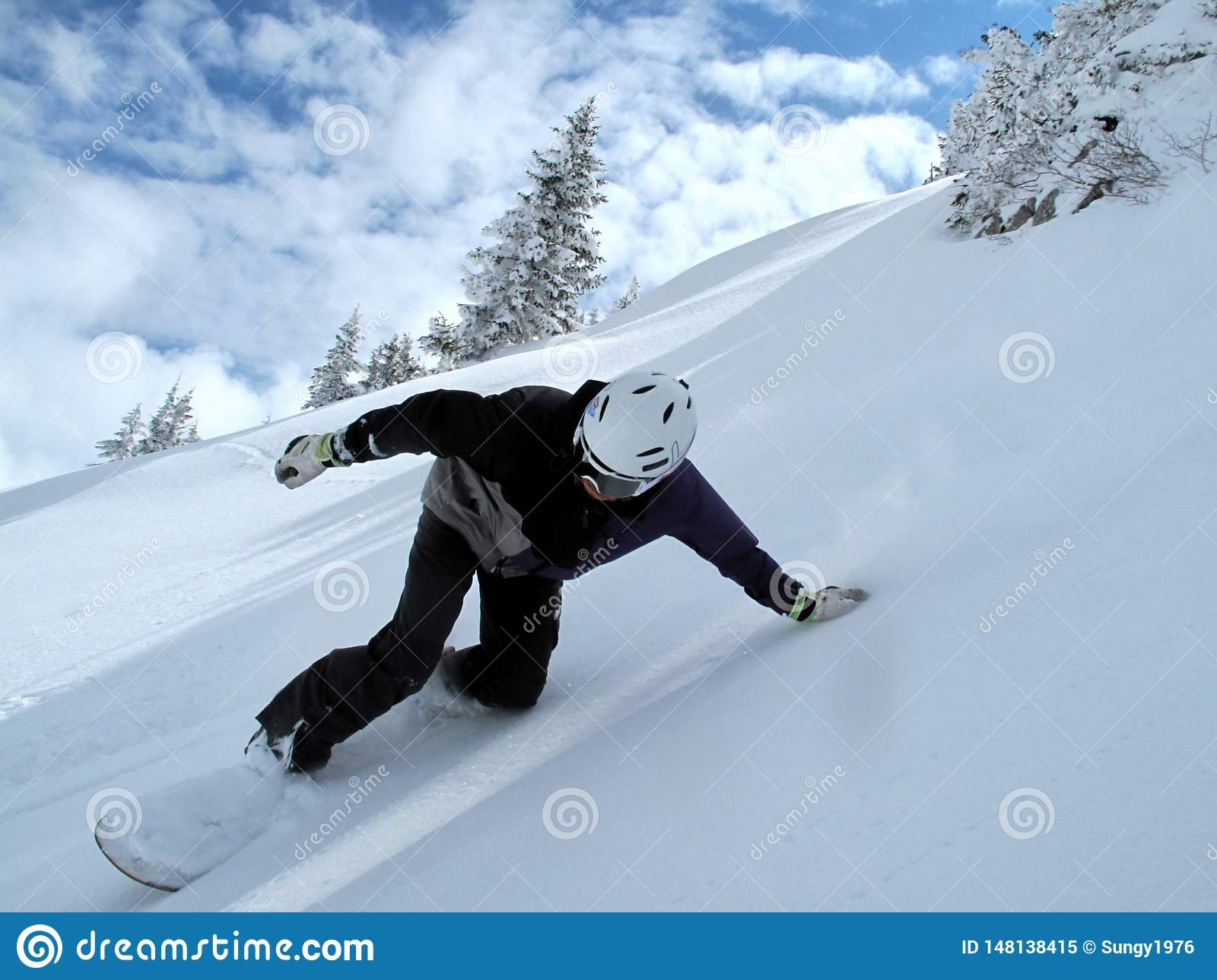 Mountain with clouds and snow, snowboarder in full speed