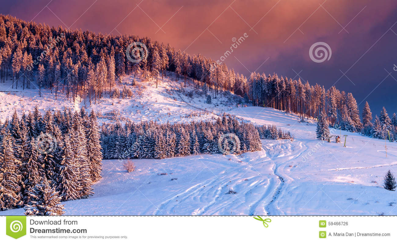 winter scene. colorful sunset over snow covered trees in an idyllic mountain landscape