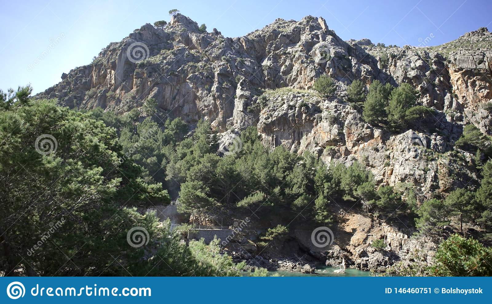 Mountain landscapes covered with green vegetation against blue sky. Art. Rocky cliff covered with trees and shrubs on