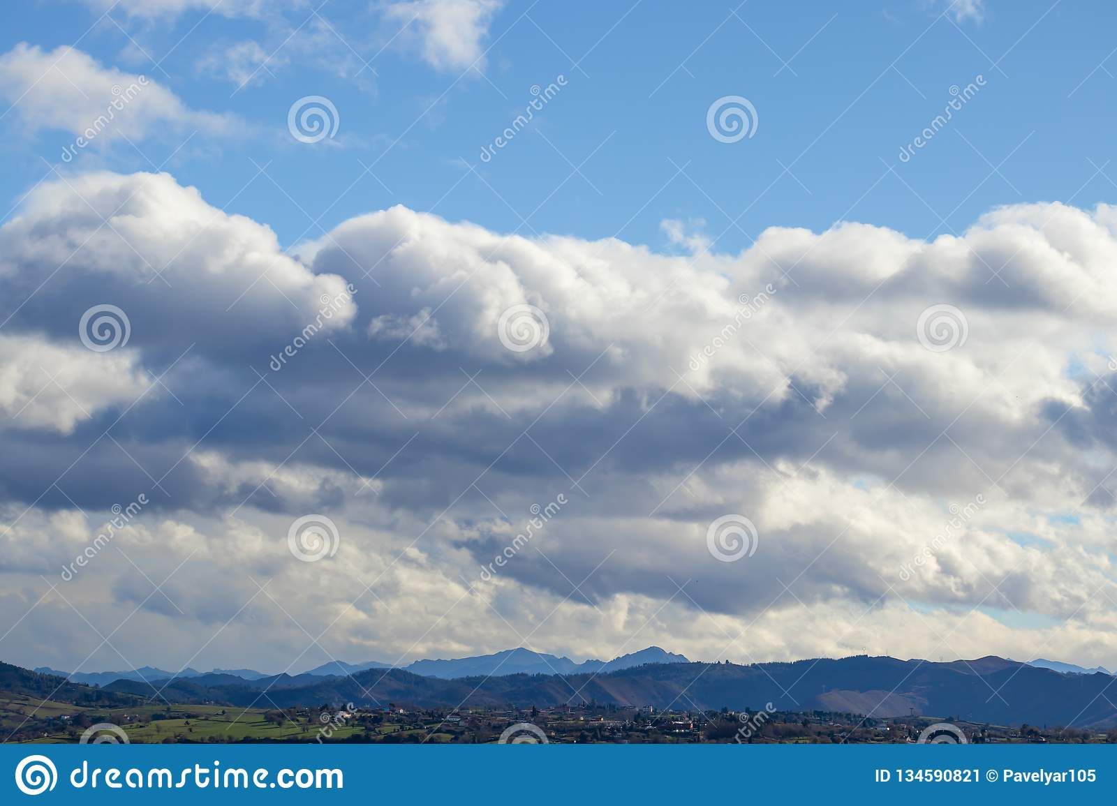 Mountain range in clear weather in contrasting rain clouds before the rain