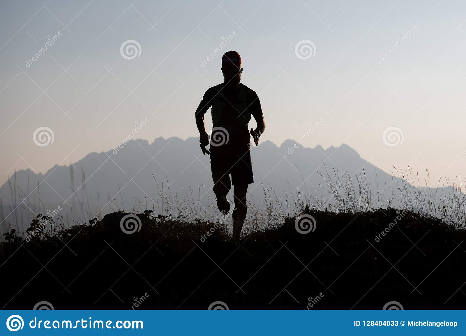 Mountain runner in silhouette in a suggestive landscape