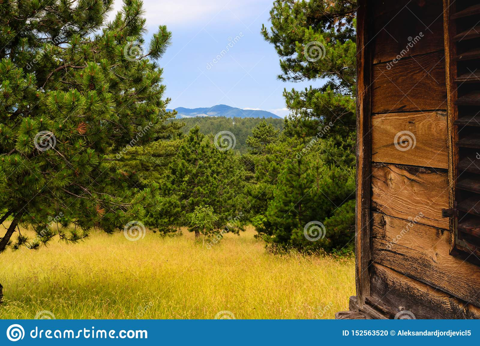 Mountain scenery behind old wooden cottage