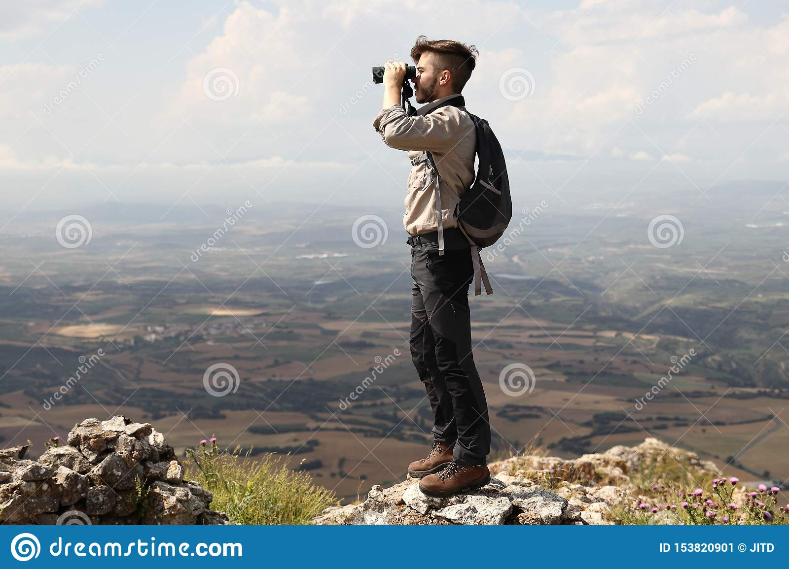 CLIMBER BOY WITH BACKPACK LOOKING WITH BINOCULARS FROM THE SUMMIT OF THE MOUNTAIN ON SUMMER HOLIDAY