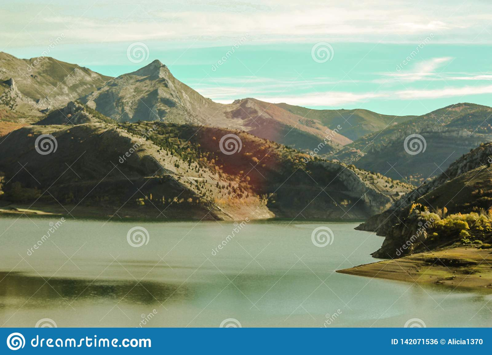 Mountainous natural landscape with lake in foreground, land of different colors